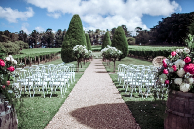This is a gorgeous ceremony space with perfectly manicured trees and bold florals
