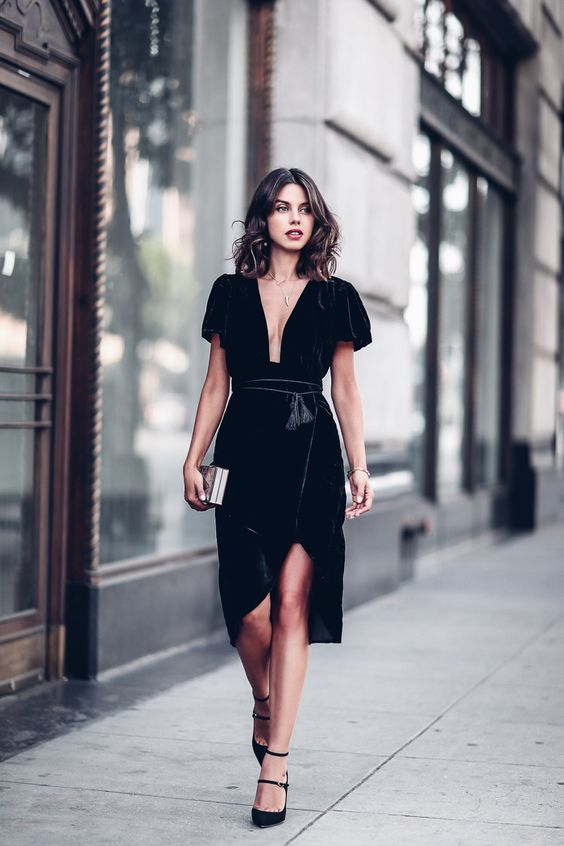 a black velvet dress with short sleeves, a plunging neckline, a tassel sash, black strappy heels