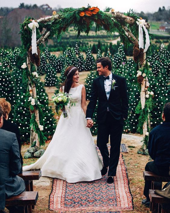 a gorgeous wedding ceremony space with lots of trees with lights and a fir branch arch