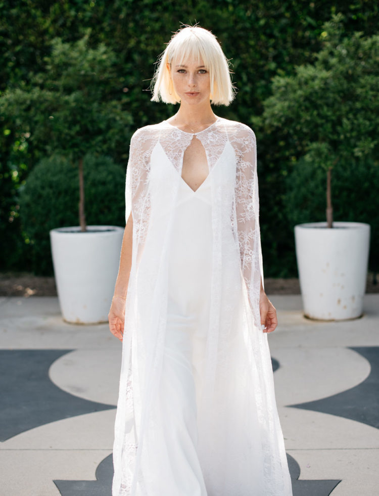 a modern spaghetti strap wedding dress with a plunging neckline and a lace cape over the dress