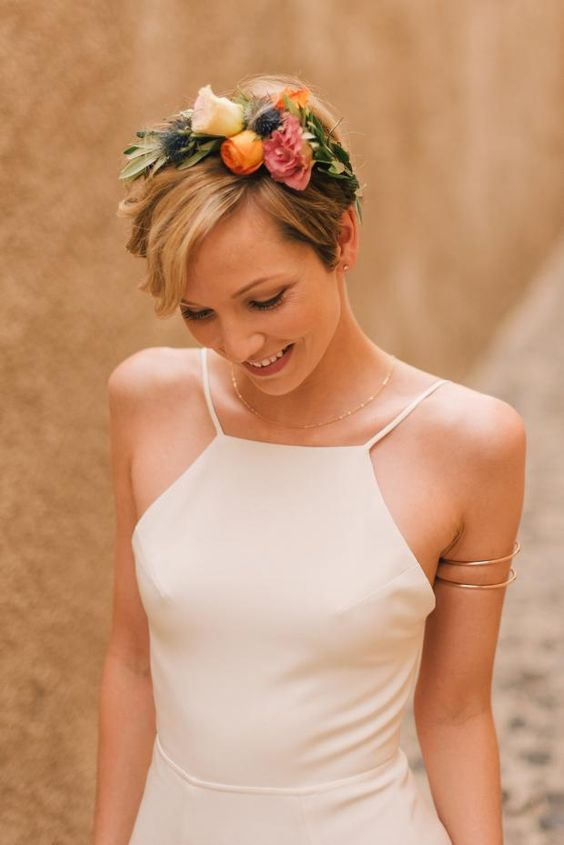 a short haircut accessorized with a colorful fresh flower headband of pink, orange, white flowers, greenery and thistles