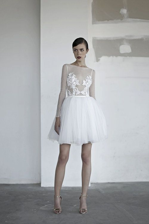 a short wedding gown with an illusion bodice and lace appliques on it, long illusion sleeves and a layered skirt