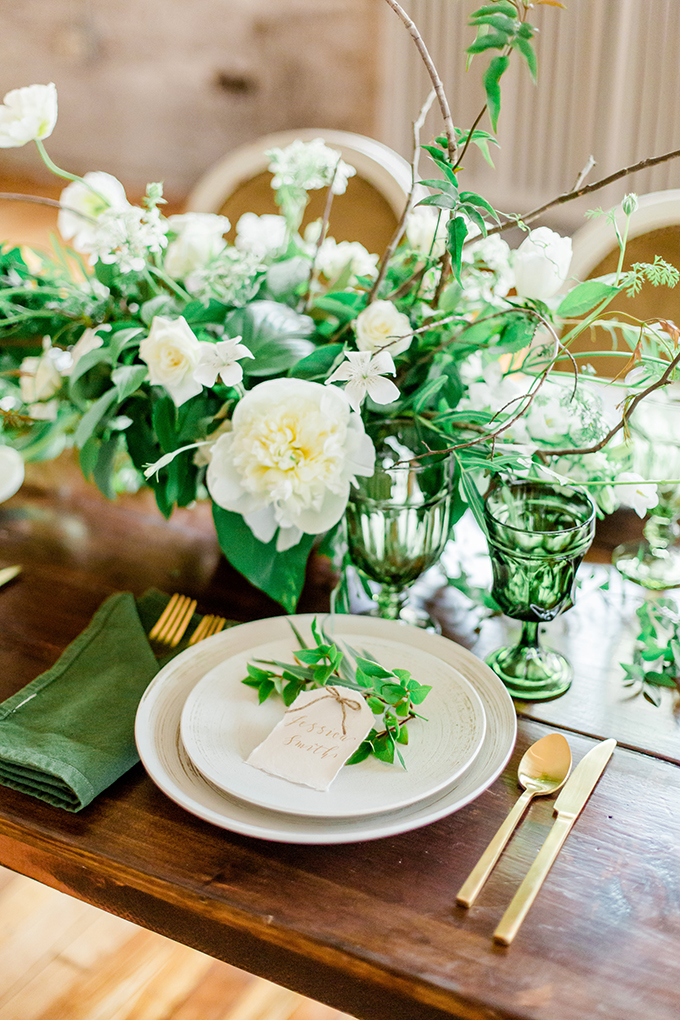 Green napkins, glasses, a fresh greenery and white bloom centerpiece were the base of the table decor
