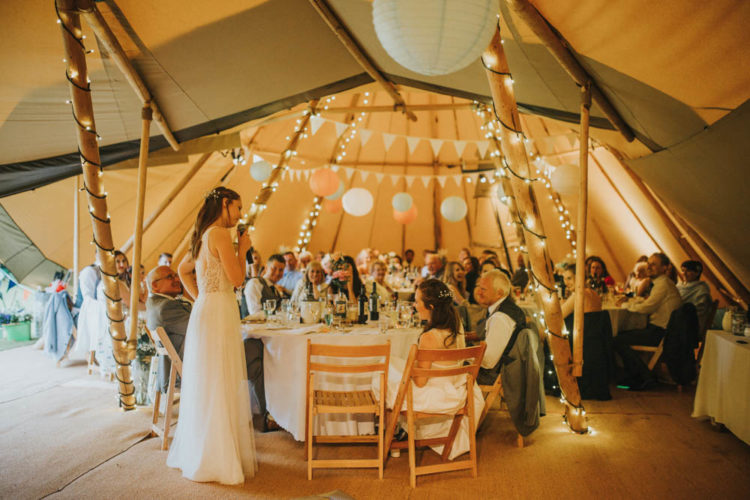 The reception took place in a rustic festival-inspired teepee with lots of lights and banners