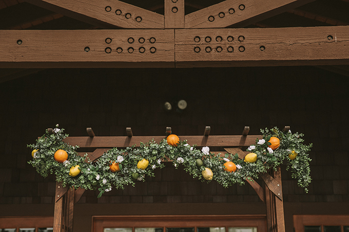 The wedding arch was topped with fresh greenery, white blooms and some citrus to fit the wedding theme
