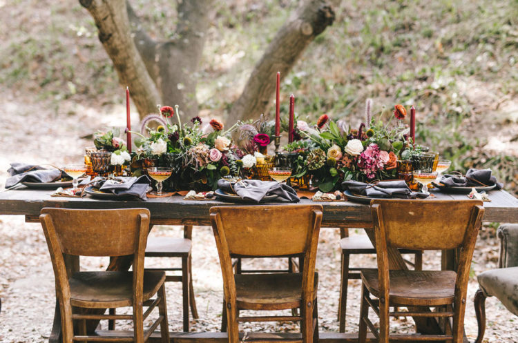The wedding tablescape was done in rich deep fall tones, with dark napkins and red candles and lush florals