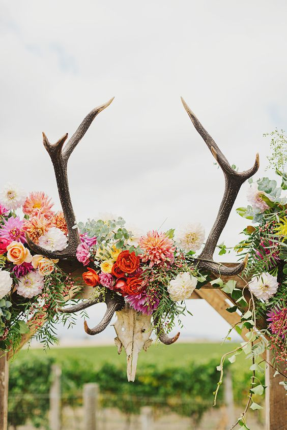 a boho wedding atch with bold blooms, foliage and antlers looks cool and bold