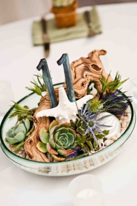 a glass bowl with driftwood, succulents, starfish and table numbers will be amazing on a beach wedding table