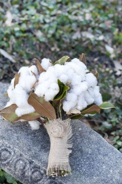 a wedding bouquet with cotton and magnolia leaves and in a burlap wrap looks super cute