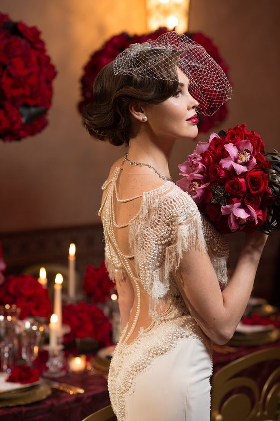gorgeous pearl and fringe detailing on the back and shoulder of the dress, pearl studs and a birdcage veil make her look wow