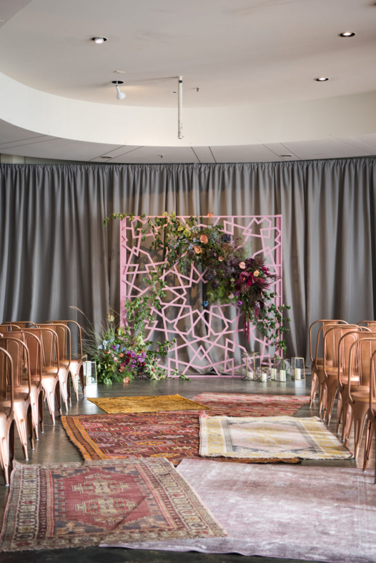 The wedding backdrop was a pink geometric one, with lush greenery and blooms, copper chairs