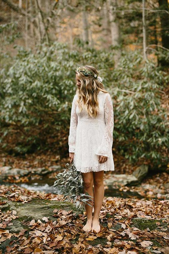 a boho lace wedding dress with long sleeves and a modest neckline, the length is over the knee