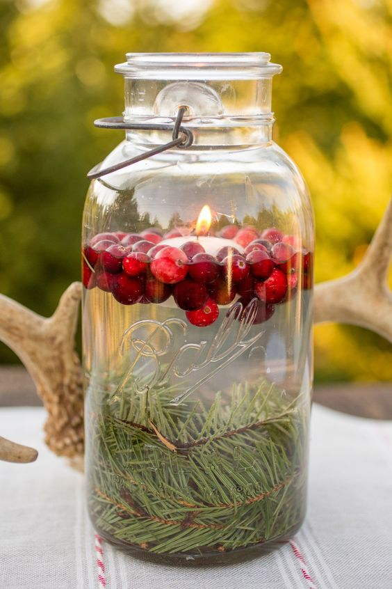 a floating candle in a jar with cranberries and evergreens looks very cute and cozy