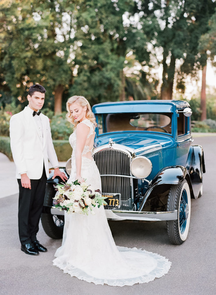 a groom wearing a tux with a white dinner jacket and a bride rocking a cutout back lace wedding dress and retro waves