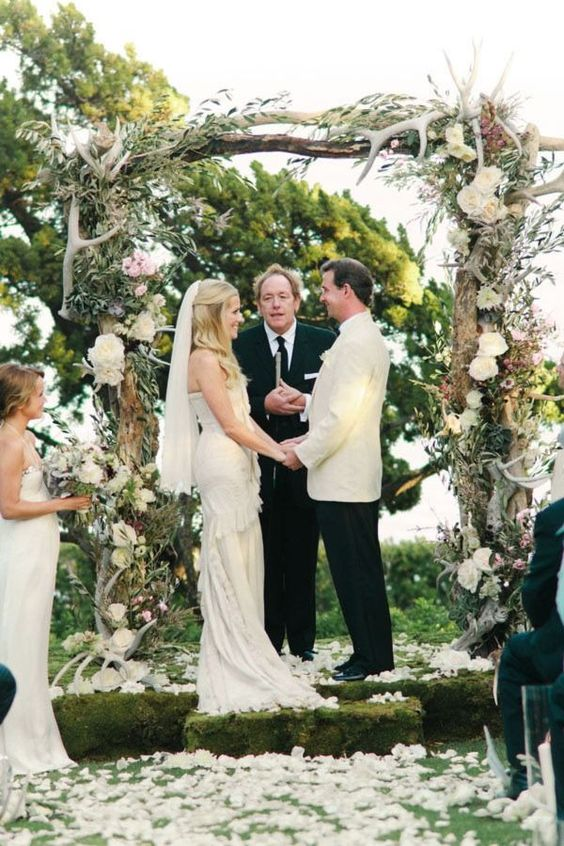 a lush woodsy wedding arch with foliage, white blooms and antlers looks wow
