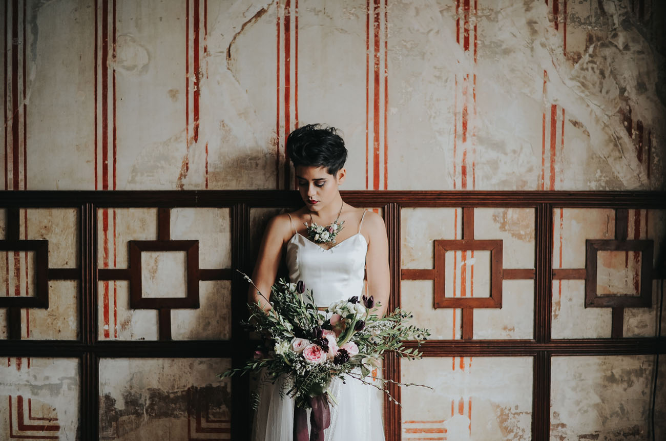 a modern daring bride with a textural pixie haircut, a bold lip and fresh floral accessories