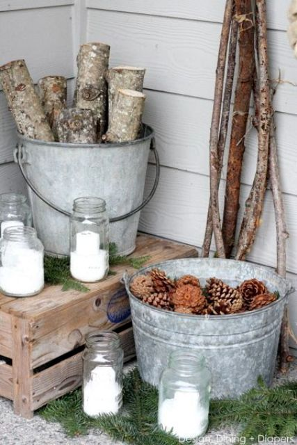 some tree branches and pinecones in metal bathtubs and candles in jars look cute and very cozy