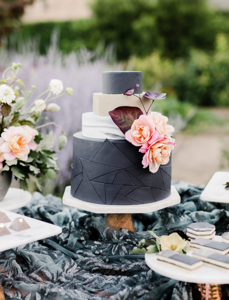 A gorgeous geometric wedding cake in matte black and white with pastel blooms