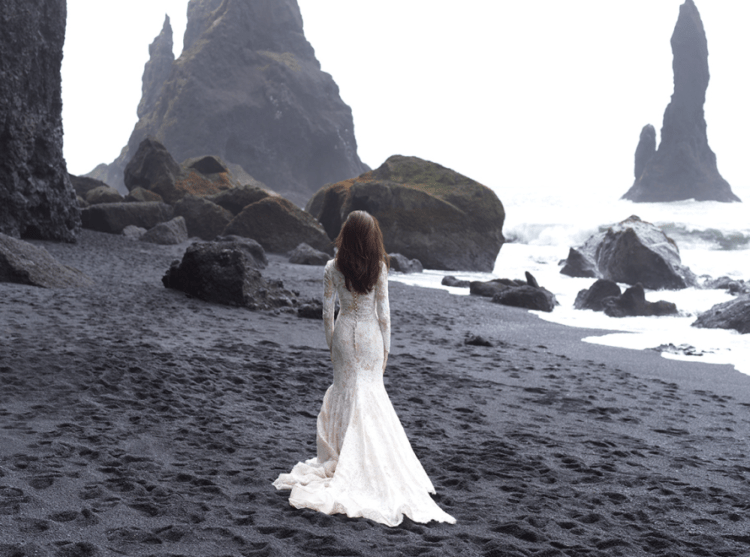 A lace mermaid wedding dress with long sleeves, a small train and a row of buttons on the back