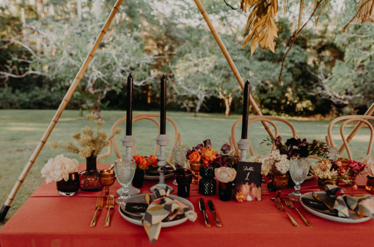 The wedidng table was laid with an orange tablecloth, black candles, bold blooms and herbs