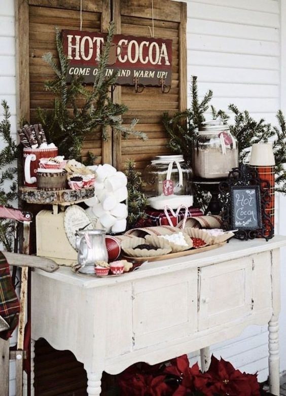 a chic hot chocolate bar with fir branches, wood slices, jars with sweets and plaid napkins