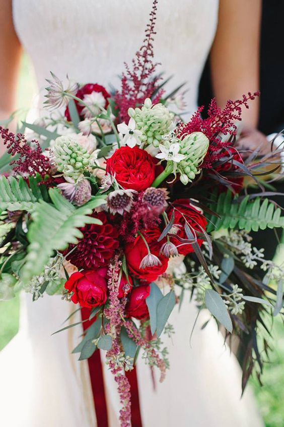 a lush bouquet with greenery, red and deep red blooms looks very textural