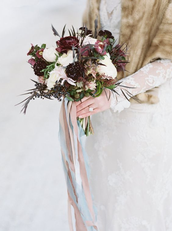a moody winter bouquet with white and burgundy blooms, greenery and privet berries with neutral ribbons of various shades