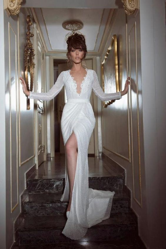 a stunning beaded wedding dress with long sleeves, a plunging neckline and a front slit for a badass bride