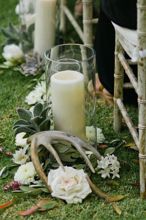 aisle decor with white blooms, pillar ccandles and antlers is a cool idea to rock for the fall