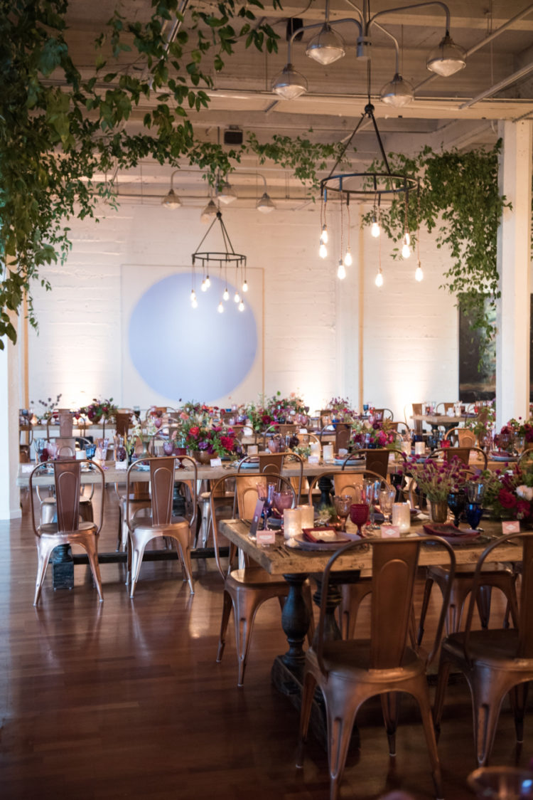 The wedding reception was done with vintage wooden tables, metal chairs, industrial chandeliers and greenery