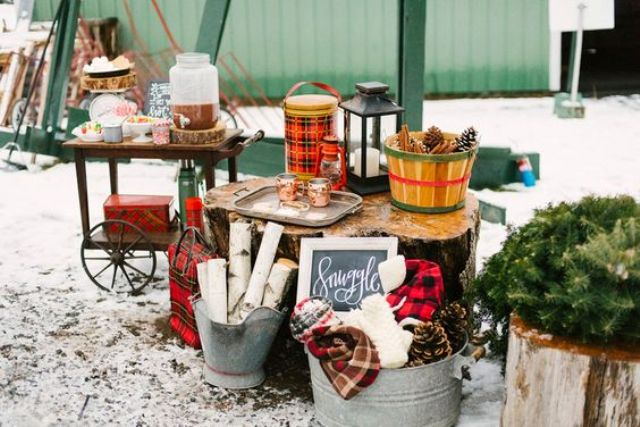 a cozy hot chocolate station with pinecones,branches, plaid blankets and fir branches