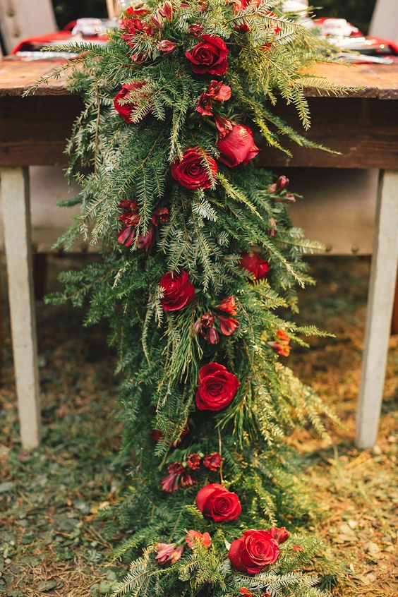 a lush evergreen table runner with red roses looks stunning on any table and adds rustic chic