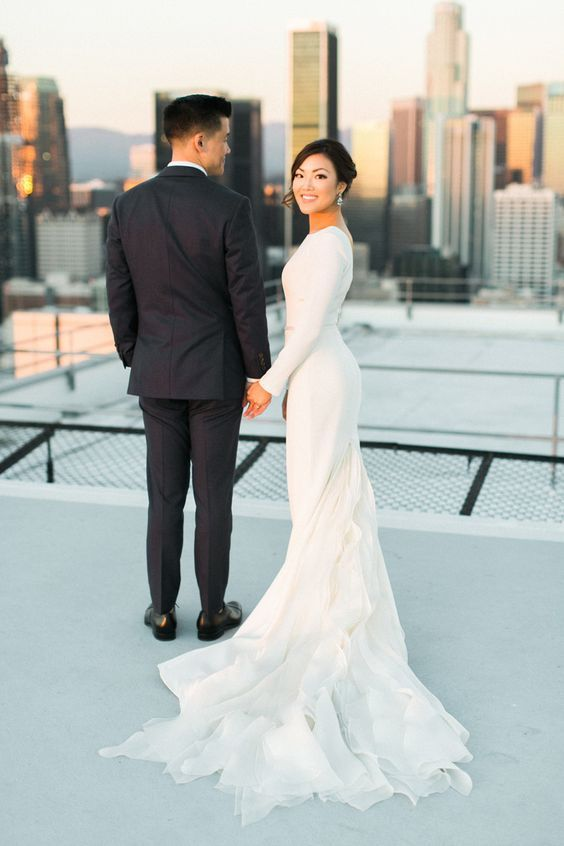 a modern wedding dress with long sleeves, a bateau neckline and a ruffled skirt and train