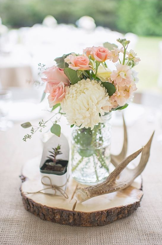 a rustic wedding centerpiece with a wood slice, a succulent, antlers and pastel blooms