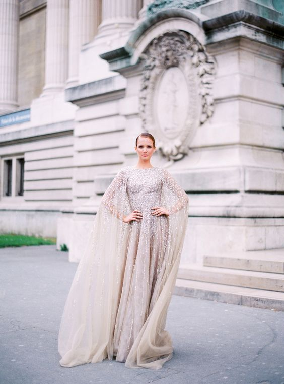 a silver glitter wedding dress with a cape attached is a bold sparkly statement
