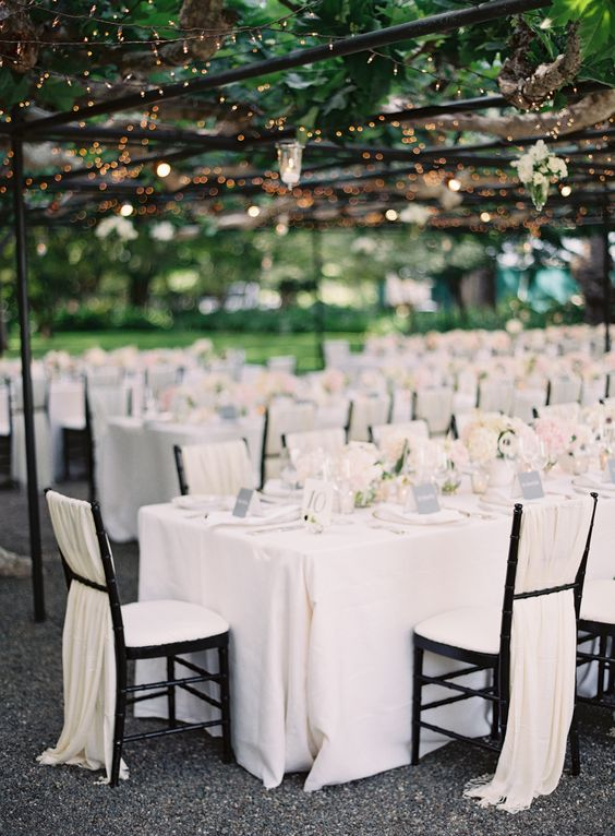 an all-white wedding looks amazing with ivory fabric on the chairs to achieve a gorgeous clean look