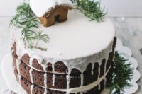 10 naked gingerbread wedding cake with icing, greenery and a gingerbread house with frosting