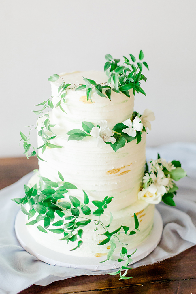 The wedding cake was a white one topped with fresh greenery and white blooms