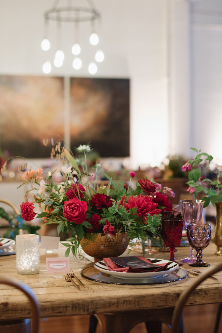 The wedding florals and glasses were jewel toned, red, burgundy and purple