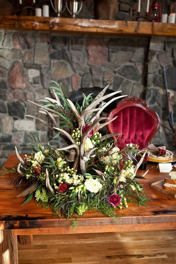 a boho woodland winter wedding centerpiece with antlers, feathers, foliage and white and pink blooms