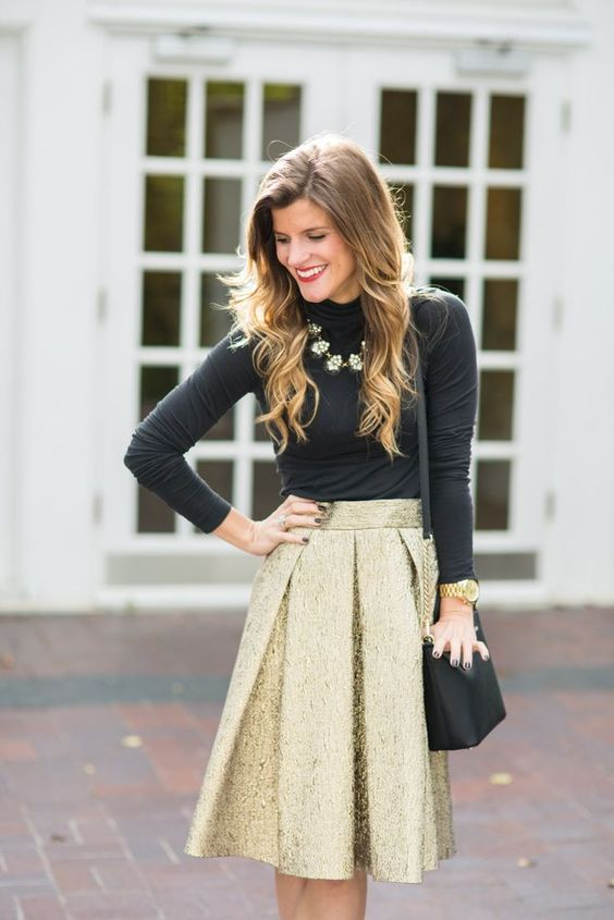 a gold pleated skirt, a black turtleneck, a statement necklace and a black and gold bag
