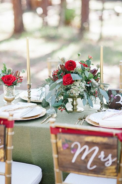 a lush greenery and red bloom centerpiece is great for a Christmas wedding