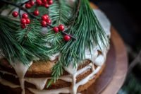 11 a naked wedding cake with white dripping, evergreens and cranberries for a relaxed Christmas wedding