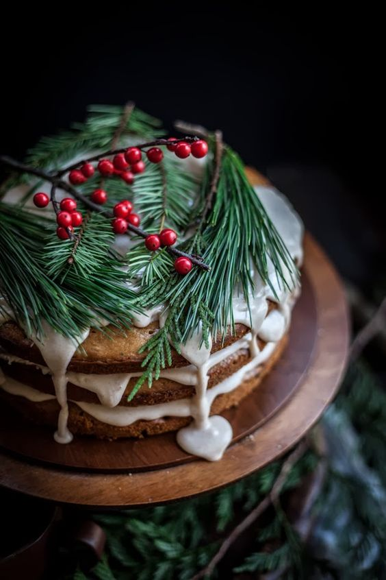 a naked wedding cake with white dripping, evergreens and cranberries for a relaxed Christmas wedding