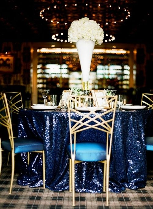 a navy sequin tablecloth, gold details and a tall white bloom centerpiece for a glam wedding