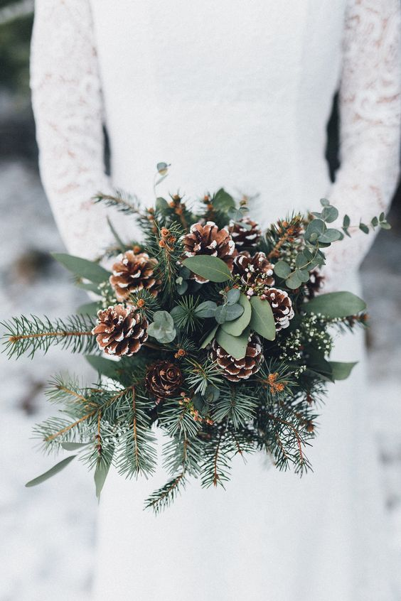 a wedding bouquet with evergreens, foliage and snowy pinecones for a winter boho or rustic bride