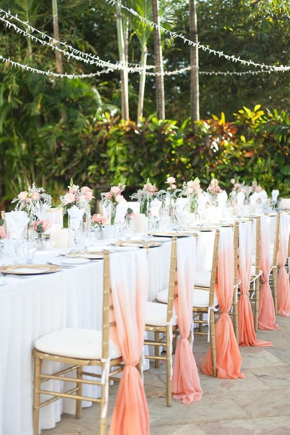 ombre coral fabric chair covers for a tropical destination wedding and coral blooms to match