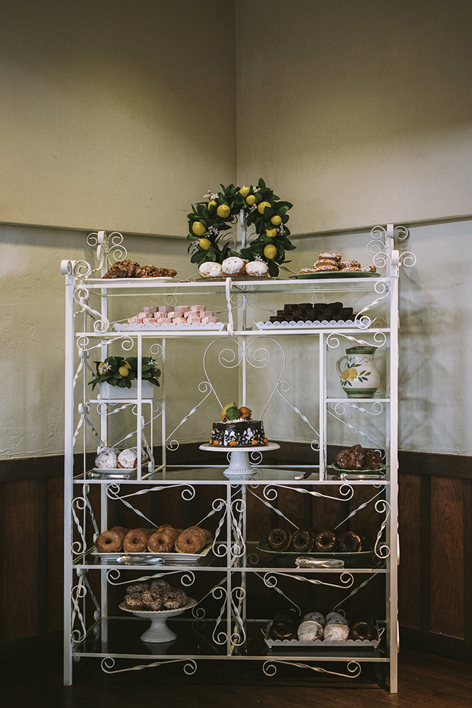 Vintage-inspired dessert table with lots of brownies, glazed donuts, buns and a wedding cake