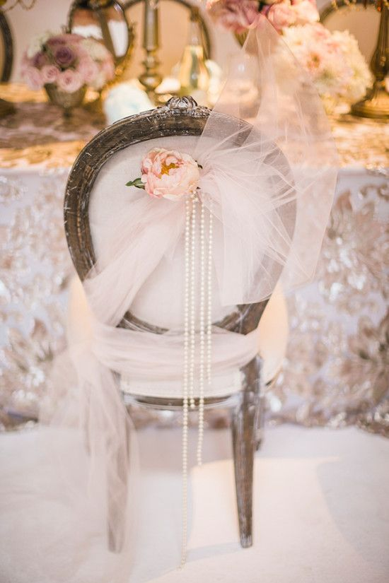 a chair covered with tulle, a blush bloom and strands of pearls for a glam vintage wedding