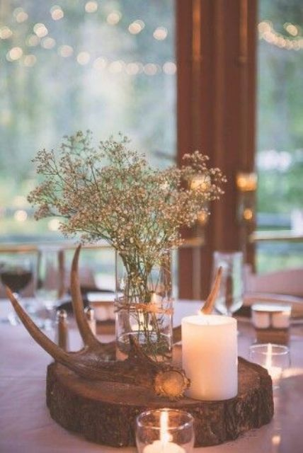 a cozy rustic wedding centerpiece with a wood slice, a candle, antlers and some baby's breath in a vase